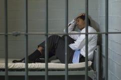 Uomo che si siede in cella di prigione Fotografie Stock
