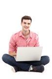 Uomo che si siede con il computer portatile Immagine Stock