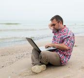 Uomo che si siede con il computer portatile Immagini Stock Libere da Diritti