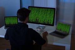 Uomo che si siede con il computer portatile ed il computer Fotografie Stock Libere da Diritti