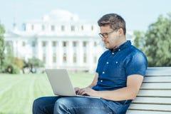 Uomo che si siede con il computer portatile fuori dell'ufficio Fotografia Stock Libera da Diritti