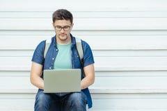 Uomo che si siede con il computer portatile fuori dell'ufficio Fotografia Stock