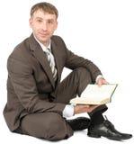 Uomo che si siede con il libro Immagini Stock