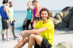 Uomo che si siede contro gli amici alla spiaggia Fotografia Stock Libera da Diritti
