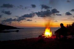 Uomo che si siede dal fuoco Immagini Stock