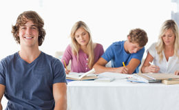 Uomo che si siede davanti ai suoi compagni della classe lavoratrice Immagini Stock Libere da Diritti