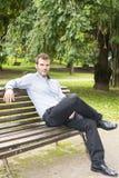Uomo che si siede e che si rilassa su un banco. Fotografia Stock