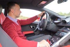 Uomo che si siede e che guida in automobile sportiva fotografie stock