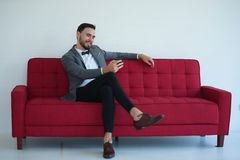 Uomo che si siede e che per mezzo di uno Smart Phone fotografie stock