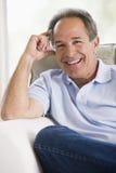 Uomo che si siede nel sorridere del salone Fotografia Stock Libera da Diritti