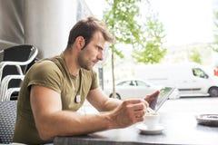 Uomo che si siede nella barra del terrazzo con la tazza di caffè e la compressa del computer portatile fotografia stock libera da diritti