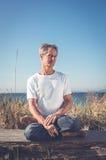 Uomo che si siede nella posa di yoga Immagini Stock Libere da Diritti