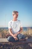 Uomo che si siede nella posa di yoga Fotografia Stock