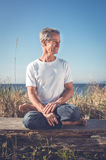 Uomo che si siede nella posa di yoga Fotografie Stock