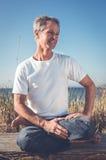 Uomo che si siede nella posa di yoga Fotografia Stock Libera da Diritti