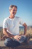 Uomo che si siede nella posa di yoga Immagini Stock