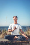 Uomo che si siede nella posa di yoga Fotografie Stock Libere da Diritti