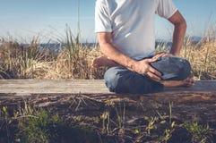 Uomo che si siede nella posa di yoga Immagine Stock