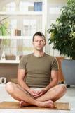 Uomo che si siede nella posizione di yoga Immagine Stock Libera da Diritti