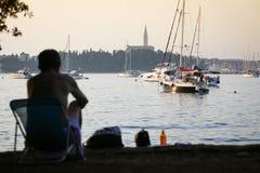 Uomo che si siede nella sedia sulla costa adriatica Fotografia Stock Libera da Diritti