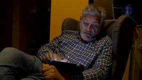 Uomo che si siede osservando compressa la notte 4K video d archivio