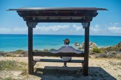 Uomo che si siede sotto il tetto che esamina mare Fotografie Stock Libere da Diritti