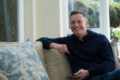 Uomo che si siede su Sofa In Living Room Fotografia Stock Libera da Diritti