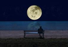 Uomo che si siede su un banco dal mare nella notte e che esamina una grande luna piena brillante con le stelle che riflettono nel immagini stock libere da diritti