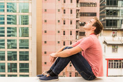 Uomo che si siede su un mensolone Fotografia Stock