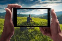 Uomo che si siede su una collina su uno schermo di smartphon immagine stock libera da diritti