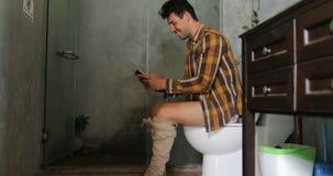 Uomo che si siede sui giovani Guy Chatting Online dello Smart Phone delle cellule di uso della toilette video d archivio