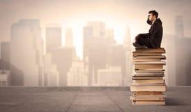 Uomo che si siede sui libri nella città Fotografia Stock Libera da Diritti