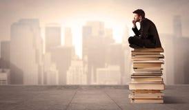 Uomo che si siede sui libri nella città Fotografie Stock Libere da Diritti