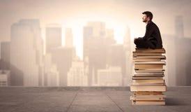 Uomo che si siede sui libri nella città Immagini Stock