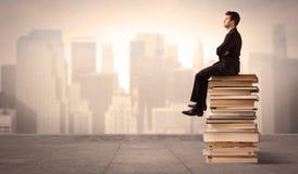 Uomo che si siede sui libri nella città Fotografia Stock