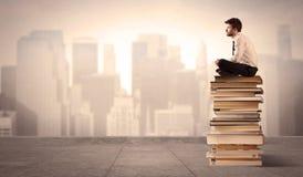 Uomo che si siede sui libri nella città Immagini Stock Libere da Diritti