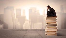Uomo che si siede sui libri nella città Immagine Stock Libera da Diritti