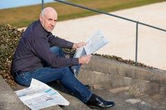 Uomo che si siede sui punti che leggono un giornale Fotografia Stock