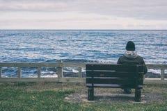 Uomo che si siede sul banco Fotografia Stock