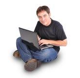 Uomo che si siede sul bianco con il computer portatile Fotografia Stock Libera da Diritti