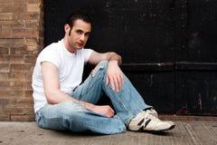 Uomo che si siede sul calcestruzzo Fotografia Stock Libera da Diritti