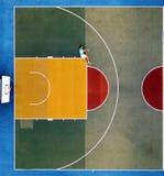 Uomo che si siede sul campo da pallacanestro fotografie stock