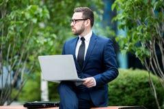 Uomo che si siede sul computer portatile della tenuta del banco fotografie stock libere da diritti
