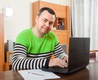Uomo che si siede sul lavoro sul computer portatile fotografie stock