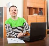 Uomo che si siede sul lavoro sul computer portatile immagine stock