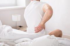 Uomo che si siede sul letto che ha dolore alla schiena Fotografia Stock Libera da Diritti