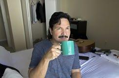Uomo che si siede sul letto che sorseggia dalla tazza Fotografia Stock