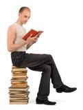 Uomo che si siede sul mucchio dei libri Fotografia Stock
