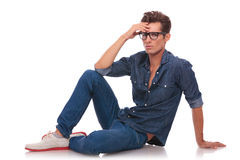 Uomo che si siede sul pavimento & sul pensiero Fotografia Stock