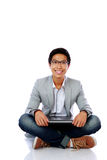 Uomo che si siede sul pavimento con il computer portatile Fotografia Stock